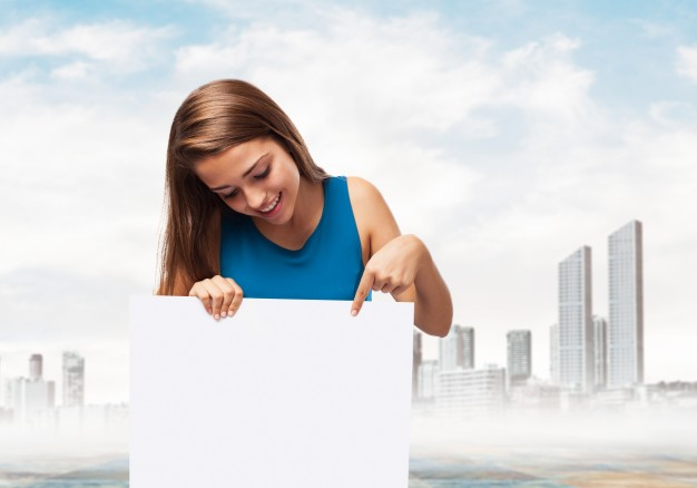 free-woman-holding-a-poster-with-a-town-background-mockup